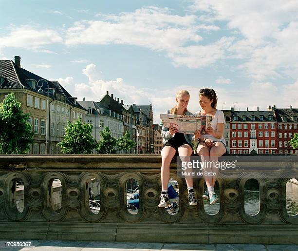 Girls sitting on bridge with city map