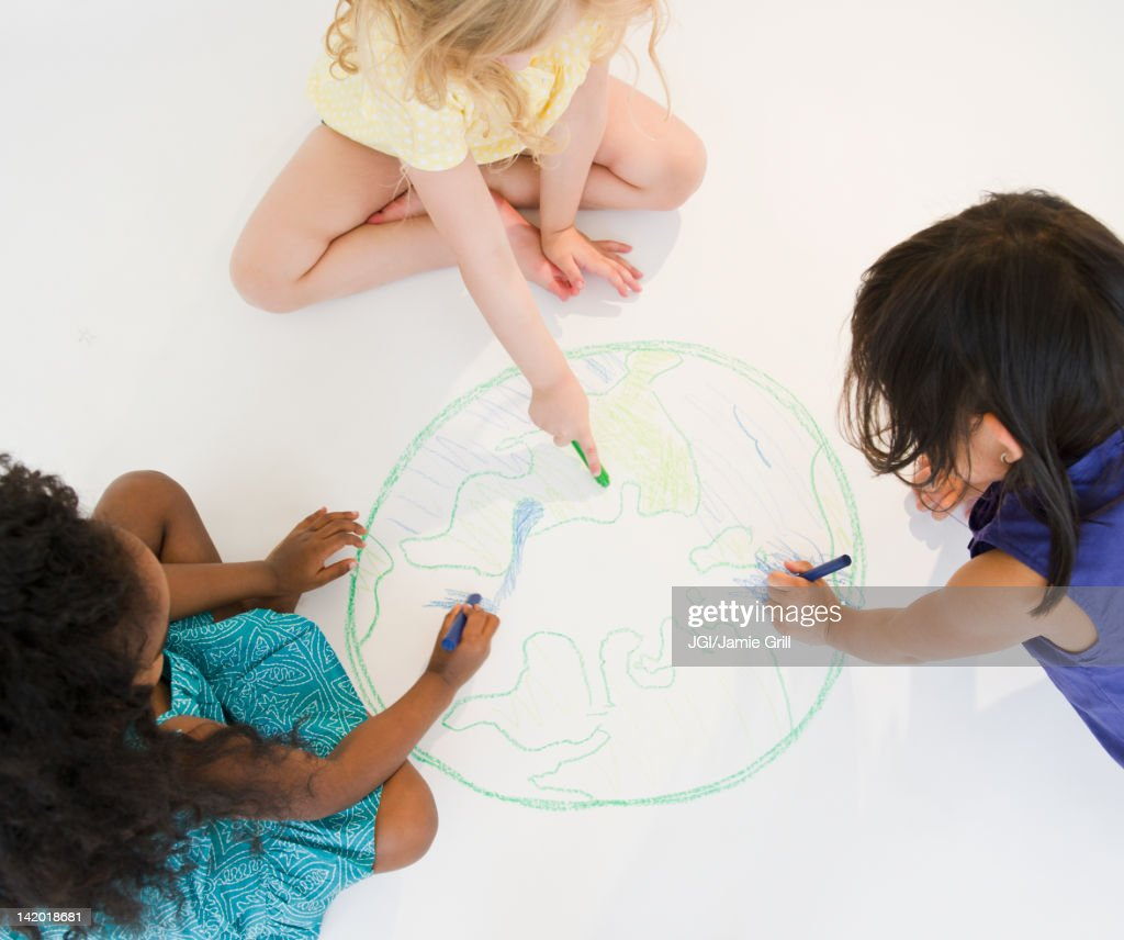 Girls sitting on floor drawing globe together : Stock Photo