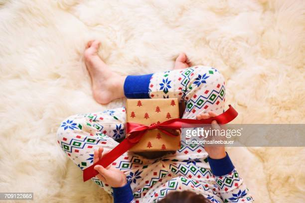 Girl's sitting on floor opening a Christmas gift
