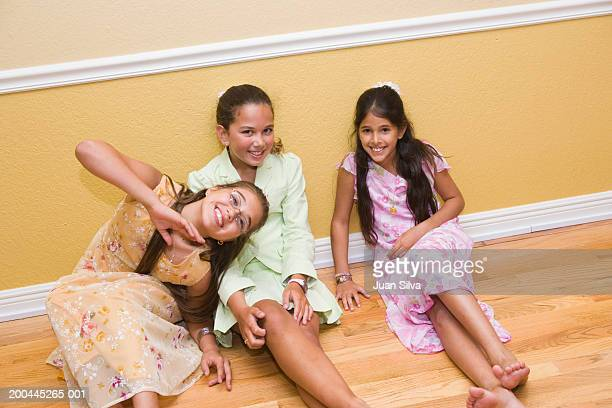 Girls (10-12) sitting on floor, smiling