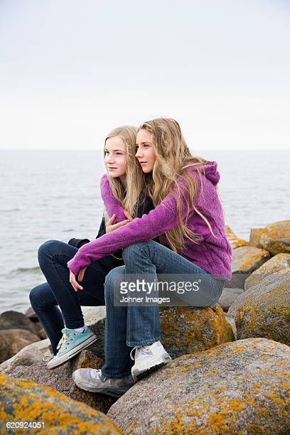girls sitting on rocks at sea - guess jeans stock photos and pictures