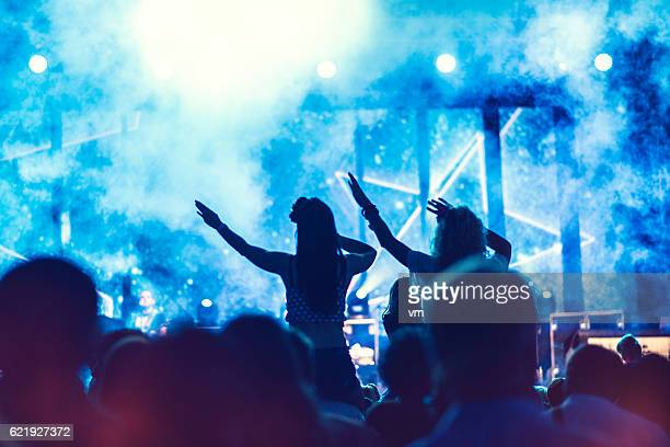 Girls sitting on shoulders at a concert
