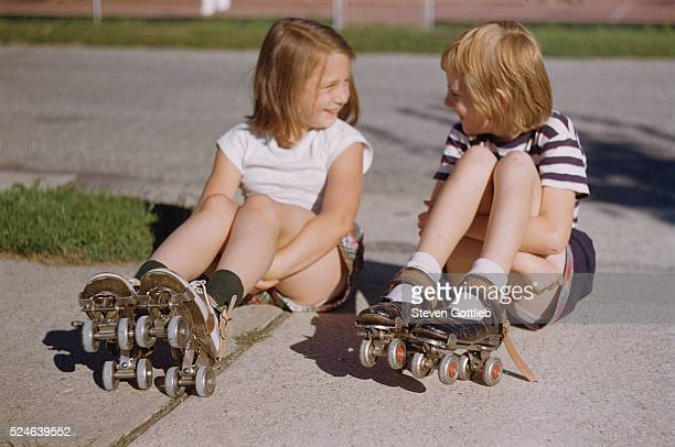 Girls Sitting on Sidewalk in Roller Skates