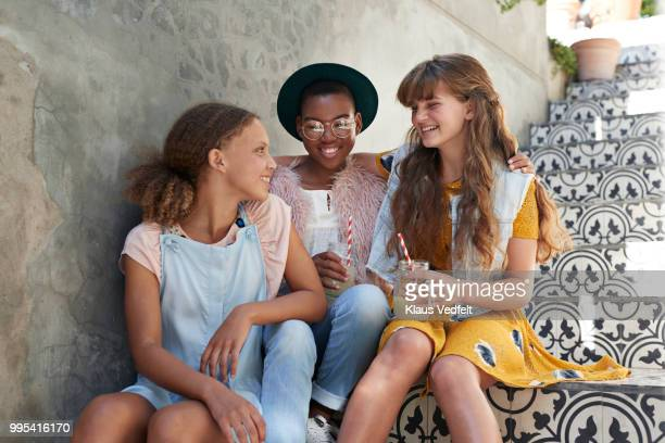 Girls sitting on staircase & chatting with lemonade