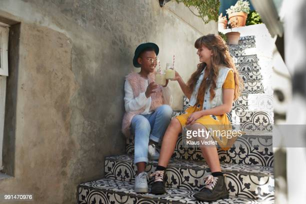 girls sitting on staircase & drinking lemonade - pink hat stock pictures, royalty-free photos & images