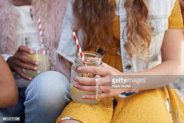 girls sitting on staircase & drinking lemonade - kaltes getränk stock-fotos und bilder