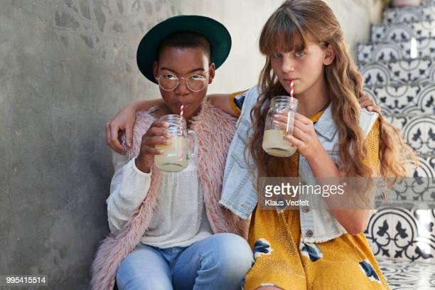Girls sitting on staircase & drinking lemonade