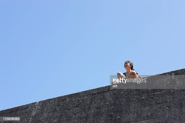 A girls sitting on the breakwater, low angle view