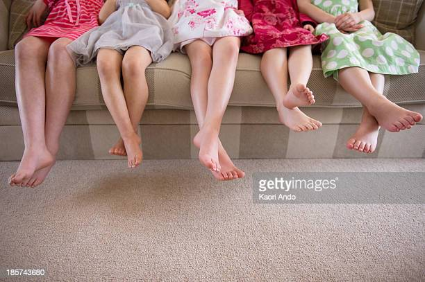 girls sitting together in a row on sofa - cobham surrey stock pictures, royalty-free photos & images