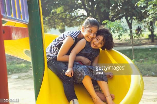 chicas deslizarse en el parque de atracciones - india summer fotografías e imágenes de stock