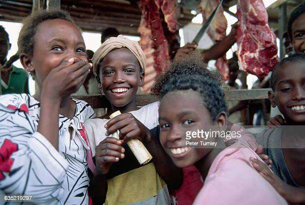Girls smile and laugh at an International Committee of the Red Cross refugee camp during the famine crisis in Somalia In the 1980s warlord factions...