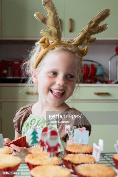 Girls smiling next to Christmas cupcakes