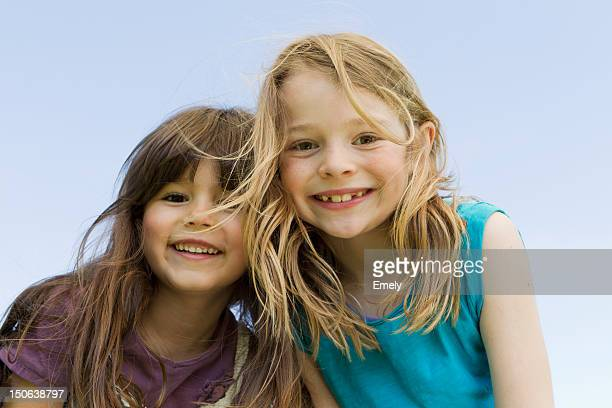 girls smiling together outdoors - nur kinder stock-fotos und bilder