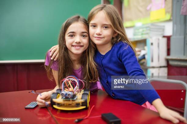 Girls smiling while making project in classroom