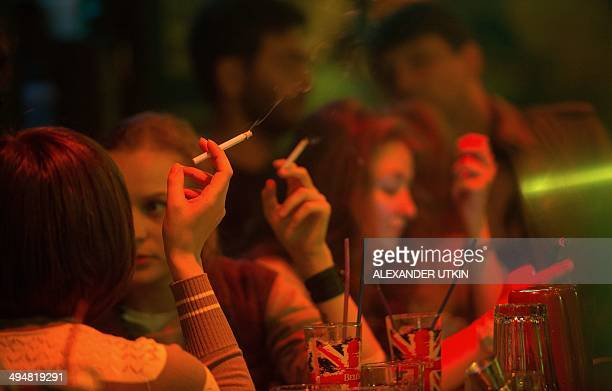 Girls smoke in a bar in central Moscow on May 30 2014 Tough new antismoking legislation that comes into force on June 1 2014 in Russia has dismayed...