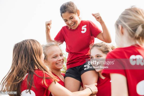 girls soccer team celebrating victory - sportmannschaft stock-fotos und bilder