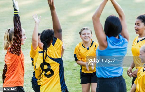 girl's soccer team, cheering with the coach - team sport stock pictures, royalty-free photos & images