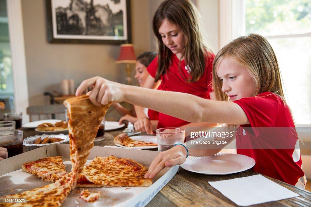 Girls soccer team eating pizza : Stock Photo
