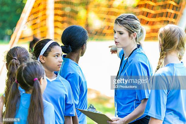 Girls soccer team listening to their coach on the sidelines