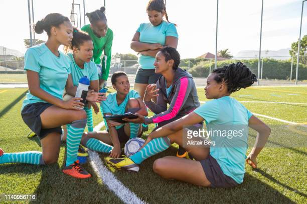 Girls soccer team listening to their female coach