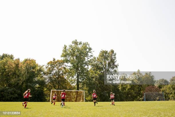 girls soccer team practicing on field on sunny day - practicing stock pictures, royalty-free photos & images