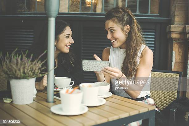Girls social networking at coffee shop in London