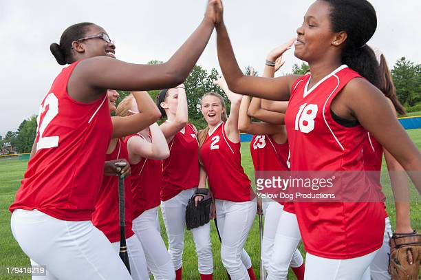 girl's softball players celebrating with high five - softball sport stock pictures, royalty-free photos & images