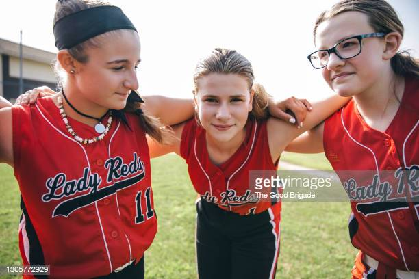 girl's softball team huddling on field before game - baseball strip stock pictures, royalty-free photos & images