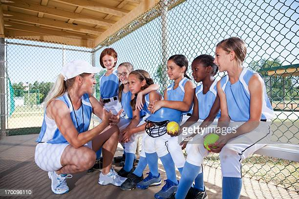 girls softball team in dugout with coach - softball sport stock pictures, royalty-free photos & images