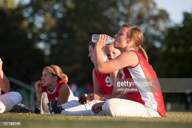 girl's softball team relaxing on the field. - softball sport stock pictures, royalty-free photos & images