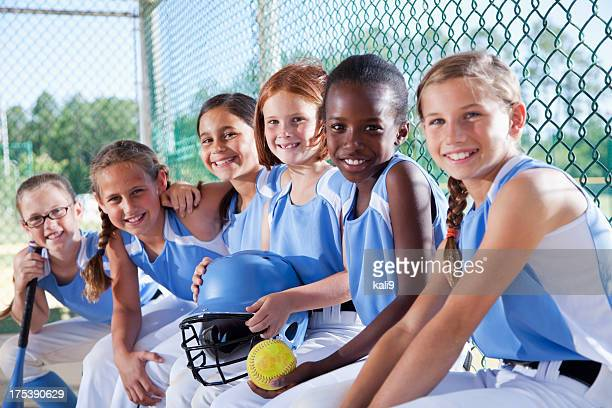 girls softball team sitting in dugout - softball stock pictures, royalty-free photos & images