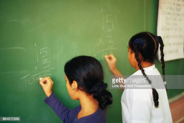 Girls Solving Arithmetic Equations on a Blackboard