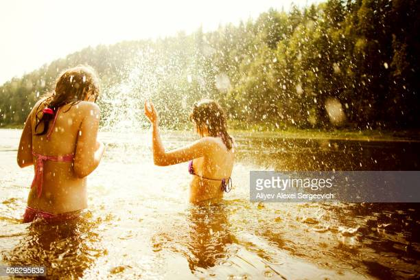 Girls splashing together in lake