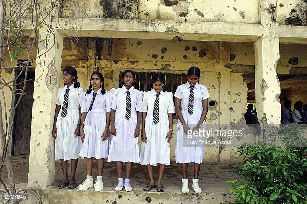 Girls stand for the school anthem at the end of the day November 12 2003 at Kilinochchi Central College in the Tamil heartland in northern Sri Lanka...
