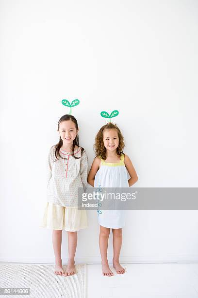 Girls standing by wall, buds are on head