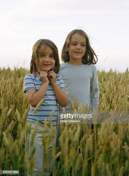 Girls standing in field, smiling
