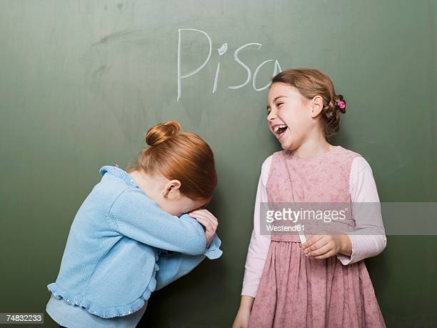 Girls (4-7) standing in front of blackboard, laughing