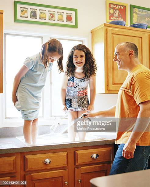 girls (5-8) standing in kitchen sink, father hosing their feet - wet t shirt girls stock photos and pictures