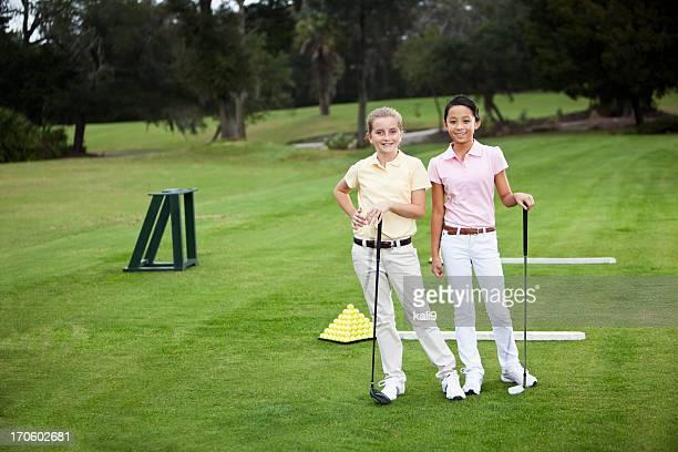 Girls standing on golf driving range
