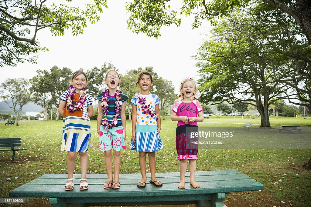 Girls standing together on picnic table : Stock Photo