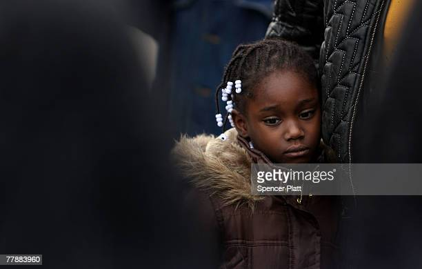A girls stands with her mother near the spot where a youth was shot and killed by a policeman November 13 2007 in Brooklyn New York After receiving a...