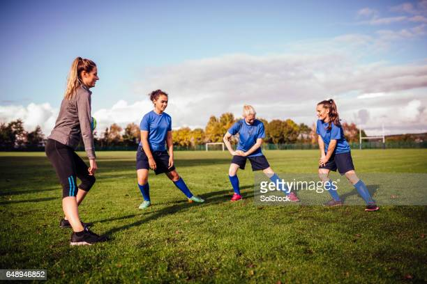 Girls Stretching on the Sports Filed