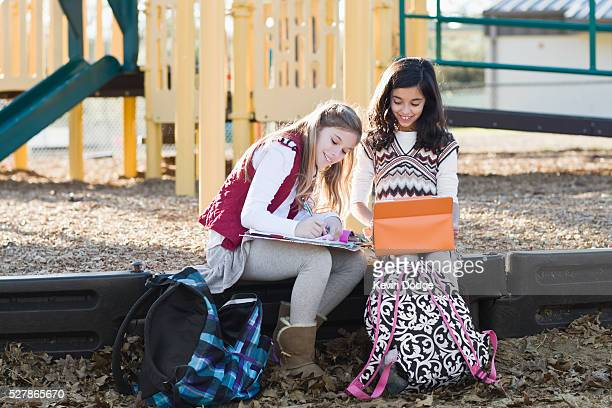 Girls (6-9) studying in playground