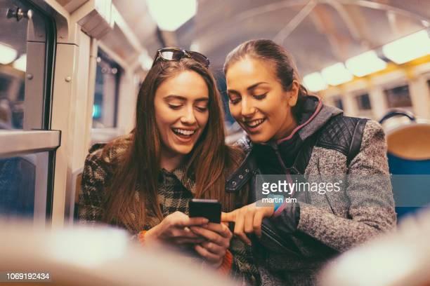 meisjes surfen op sociale media in de metro - tram stockfoto's en -beelden