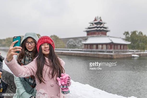Girls take a selfie with the Forbidden City's moat in the background on November 22 2015 in Beijing China Heavy snow has fallen in Beijing this...