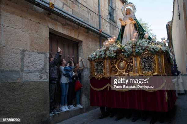 Girls take pictures of the image of Our Lady of Hope during a procession of the Jesus del Via Crucis brotherhood on April 11 2017 in Zamora Spain...