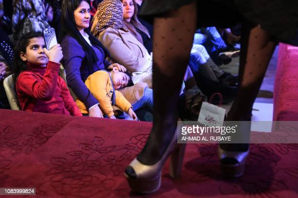 A girls takes a photograph with a mobile phone as an Iranian model presents a creation by two Iranian female fashion designers during a show at a...