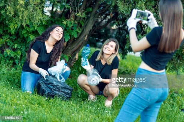 girls taking a selfie after plogging. - green glove stock photos and pictures
