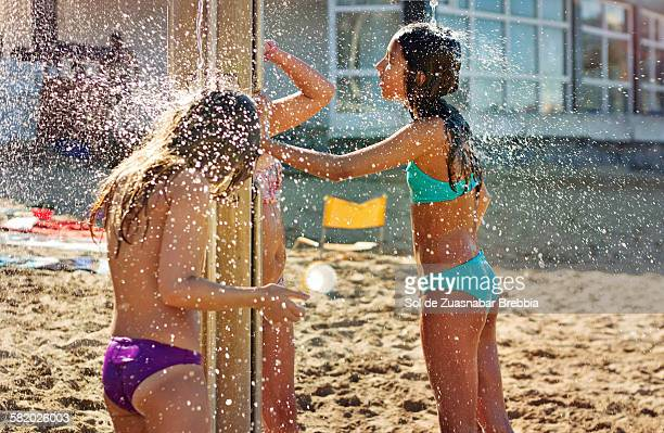 Girls taking a shower at the beach on a sunny day