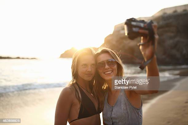 Girls taking photo of themselves on beach